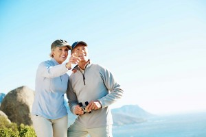 Portrait of mature man holding binoculars while woman pointing at something interesting